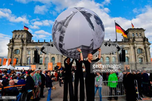 Performers on stilts carry a giant ball in front of the Reichstag building that houses Germany's Bundestag lower house of parliament in Berlin on May...