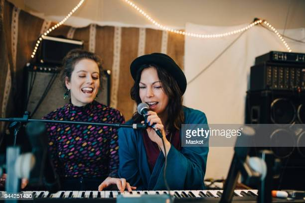 performers playing piano and singing while practicing in studio - singing stock pictures, royalty-free photos & images