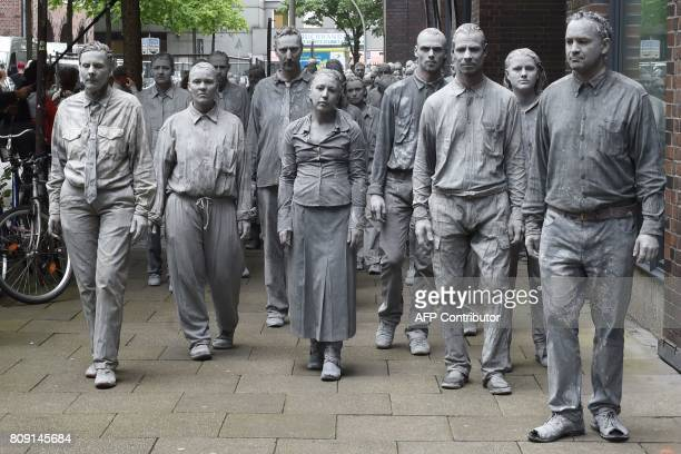 TOPSHOT Performers smeared with clay demonstrate during the art action '1000 Gestalten' on July 5 2017 on a street in Hamburg northern Germany where...