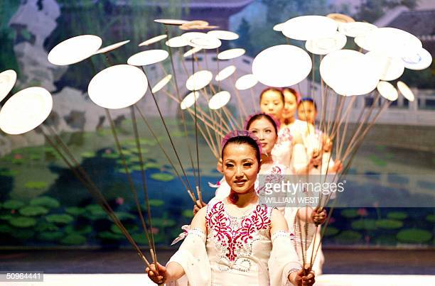 Performers spin plates from the New Shanghai Circus as they prepare for their shows in Sydney 16 June 2004. Under the direction of Zhao Lizhi, the...