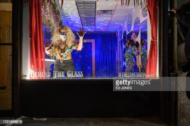 Performers stage a free production of Romeo and Juliet in a vacant shop window on a west side street in Manhattan, New York, on March 13, 2021. - The...