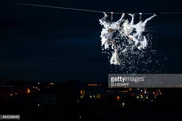 Performers suspended from highwires pour feathers onto members of the public below during the outdoor aerial performance of the show 'Place des...