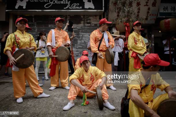Performers take a break between action during a parade for the Hungry Ghost Festival in Hong Kong on August 22 2013 The festival celebrated in the...
