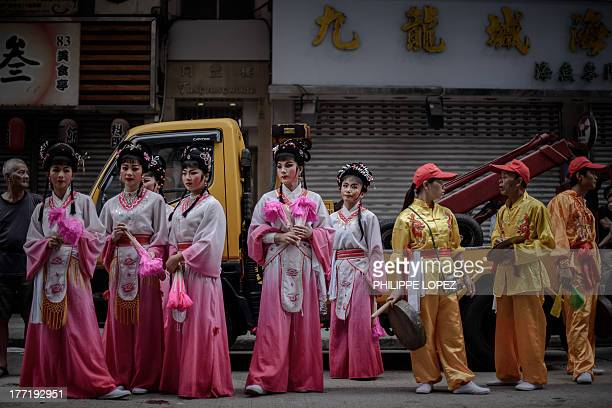 Performers take a break during a parade for the Hungry Ghost Festival in Hong Kong on August 22 2013 The festival celebrated in the seventh lunar...