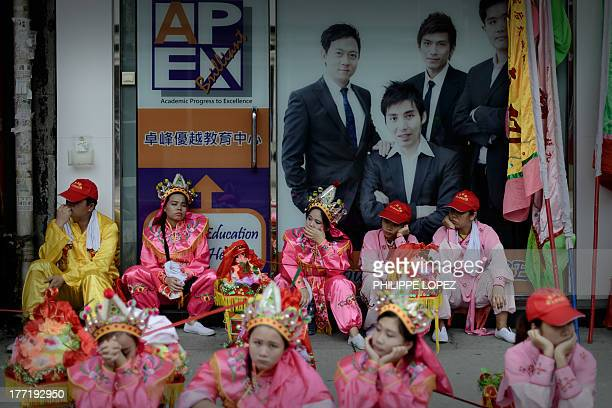 Performers take a break from the action as they participant in a parade for the Hungry Ghost Festival in Hong Kong on August 22, 2013. The festival,...