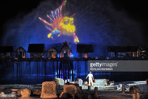 Performers take part during the last show of a pyrotechnic and laser display over a specially built kelong or fishing village during the 'Songs of...