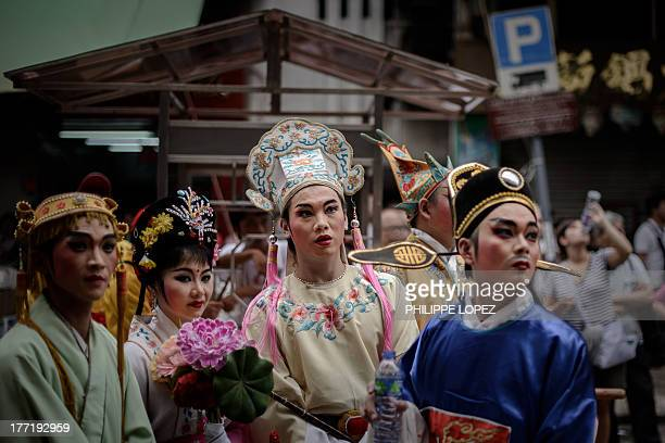 Performers take part in a parade for the Hungry Ghost Festival in Hong Kong on August 22, 2013. The festival, celebrated in the seventh lunar month...