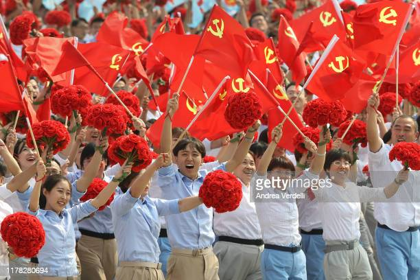 Performers walk and wave the communist flags during the parade for the 70th anniversary of the establishment of the People's Republic of China on...