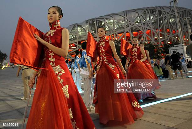 Performers walk past the National Stadium also known as the Bird's Nest during rehearsals for the 2008 Olympic Games opening ceremony in Beijing on...