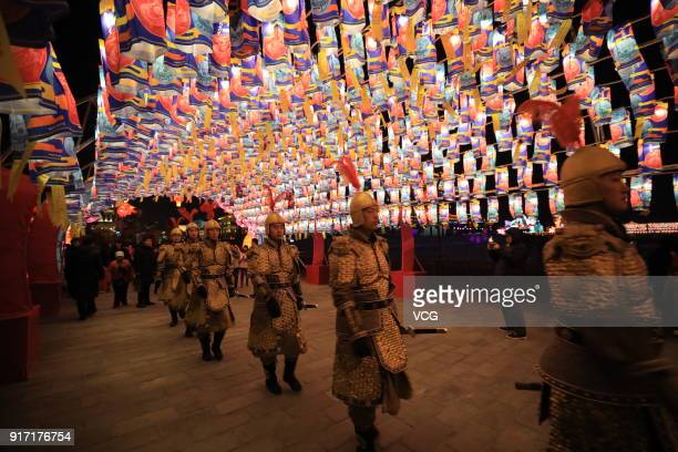 Performers walk under illuminated lanterns during a lantern fair near the Xi'an City Wall on February 10 2018 in Xi'an Shaanxi Province of China 2018...