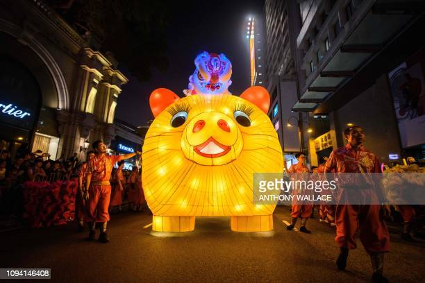 TOPSHOT Performers walk with a lit model of a pig during the annual Lunar New Year parade in the Kowloon district of Hong Kong on February 5 to mark...