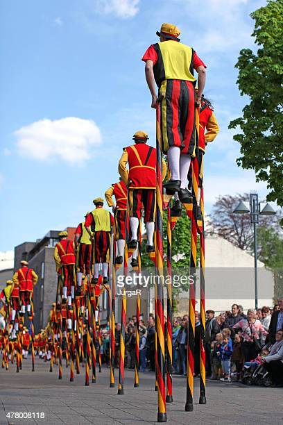 performers walking on stilts at may day parade in belgium - may day international workers day stock pictures, royalty-free photos & images