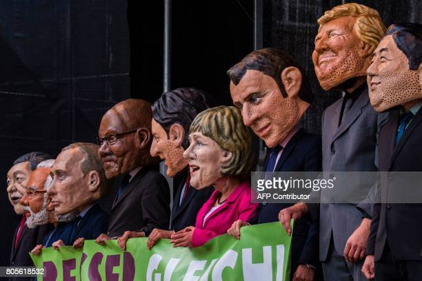 Performers wearing masks of world leaders hold a placard reading 'Better off equal Close the gap between rich and poor' during a demonstration called...