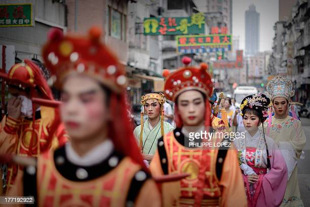 Performers wearing traditional costumes take part in a parade for the Hungry Ghost Festival in Hong Kong on August 22, 2013. The festival, celebrated...
