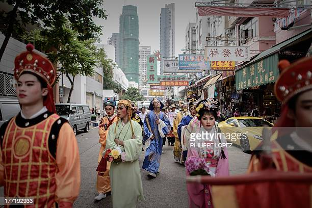 Performers wearing traditional costumes take part in a parade for the Hungry Ghost Festival in Hong Kong on August 22 2013 The festival celebrated in...