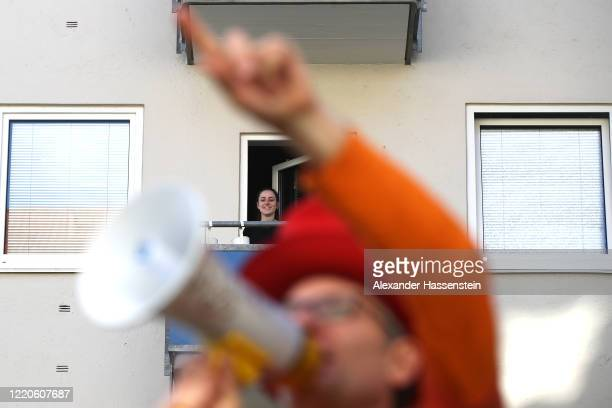 Performing artist Max Auerbach announces bingo numbers to participants playing from their balconies during the novel coronavirus crisis on April 23,...