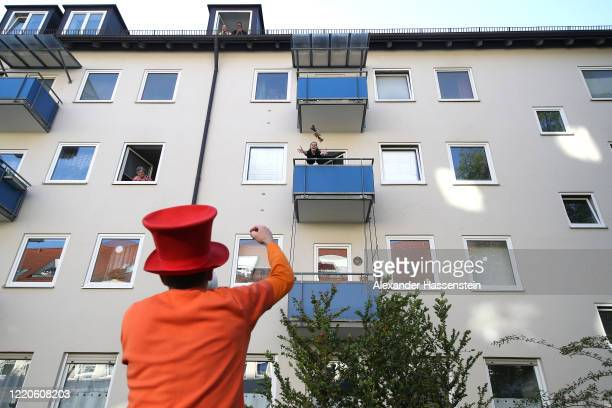Performing artist Max Auerbach throws the winning gift, a roll of toilet paper to a resident after playing bingo from their balconies during the...