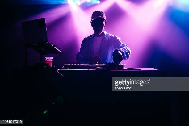 dj performing music set with light display - hip hop music stock pictures, royalty-free photos & images