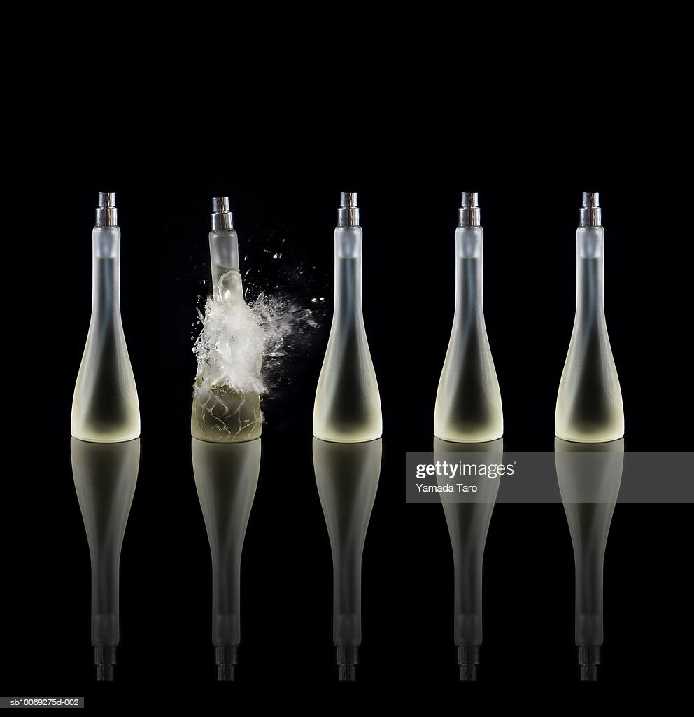 Perfume bottle in row, one exploding, close-up : Stockfoto