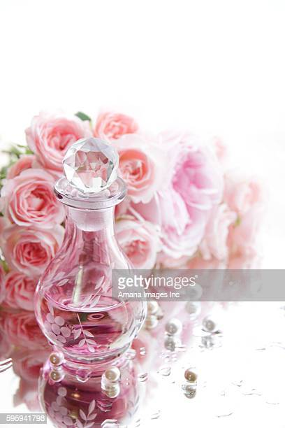 Perfume bottle on wet mirror, pink roses and pearls