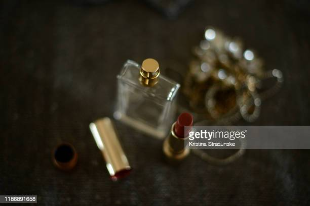 perfume bottle, red lipstick and a necklace on a dark sparkly background - kristina strasunske stock pictures, royalty-free photos & images