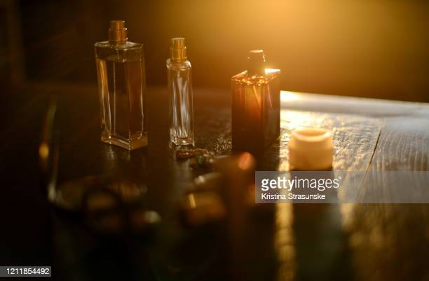 perfume bottles, necklaces and makeup products on a black background in a beautiful golden sunlight - kristina strasunske stock pictures, royalty-free photos & images