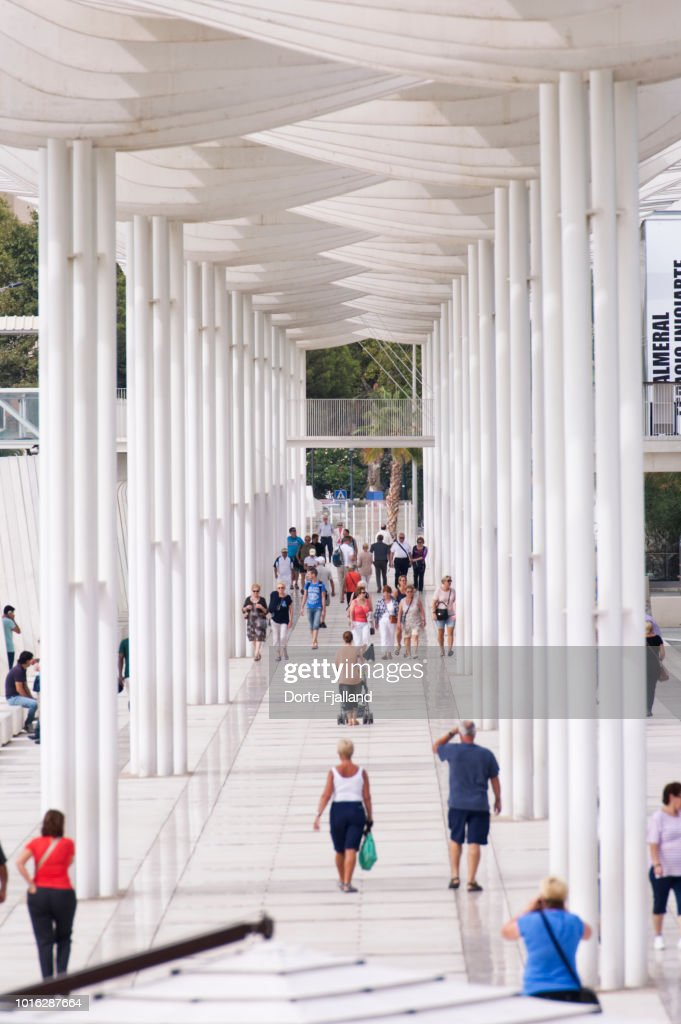 A pergola covered promenade with people walking in both directions : Foto de stock
