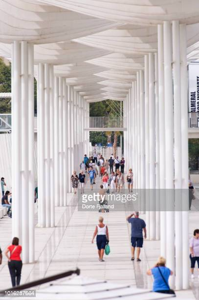 A pergola covered promenade with people walking in both directions