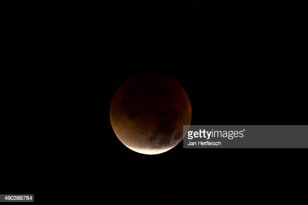 A perigee full moon or super moon is seen during a total lunar eclipse on September 28 2015 in Innsbruck Austria The combination of a supermoon and a...