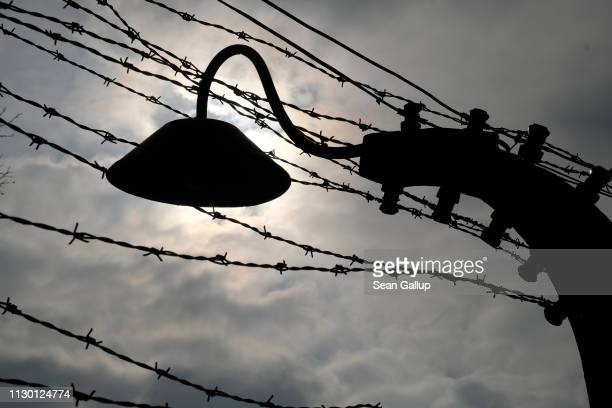 A perimeter light and barbed wire fence stand at the Auschwitz I memorial concentration camp site on February 15 2019 in Oswiecim Poland Next year...
