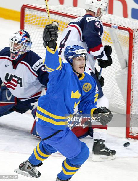 Per-Johan Axelsson of Sweden celebrates a scored goal against goalie Mike Dunham and defenseman Eric Weinreich of the USA during the Semifinals match...