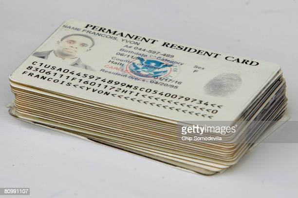 Permanent resident cards are stacked after being turned in by 25 people ahead of a natrualization ceremony on the National Mall May 5, 2008 in...