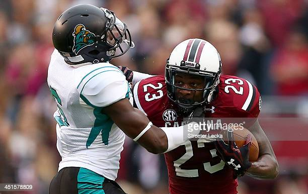Pernell Williams of the Coastal Carolina Chanticleers tries to stop Bruce Ellington of the South Carolina Gamecocks during their game at...