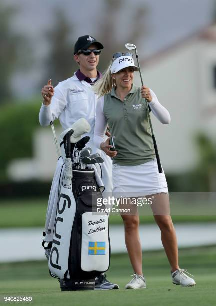 Pernilla Linberg of Sweden weaits to play her third shot on the 18th hole in the first playoff hole with her caddie and fiancee Daniel Taylor during...