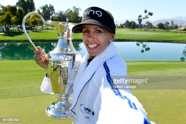 Pernilla Lindberg of Sweden imitates a selfie as she poses with the winner's trophy after defeating Inbe Park of South Korea during the sudden death...
