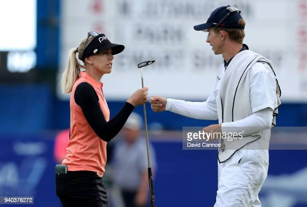 Pernilla Lindberg of Sweden knocks fists with her caddie and fiancee Daniel Taylor after her birdie on 18 secured her a three shot lead heading into...