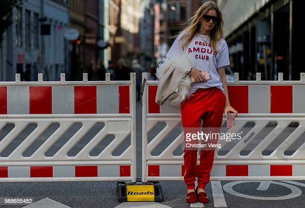 Pernille Rosenkilde wearing red Adidas tracksuit pants Gucci slipeers and a white tshirt outside Baum und Pferdgarten during the second day of the...