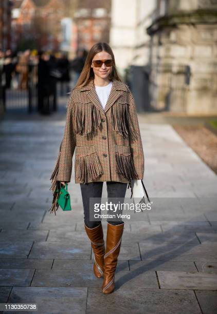 Pernille Teisbaek is seen wearing jacket with fringes, Hermes bag, brown boots, denim jeans outside Victoria Beckham during London Fashion Week...