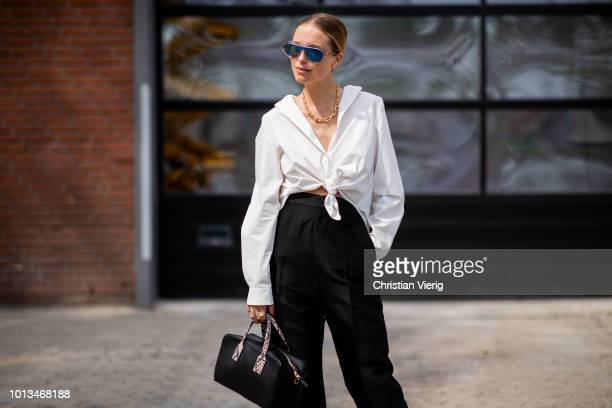 Pernille Teisbaek wearing white blouse black high waisted pants is seen outside Holzweiler during the Copenhagen Fashion Week Spring/Summer 2019 on...