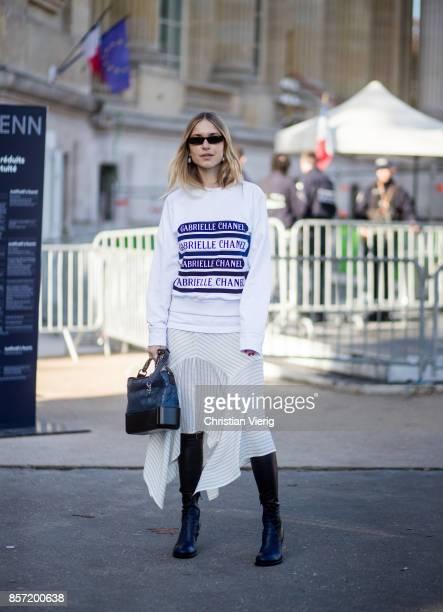 Pernille Teisbaek wearing white Chanel longshirt skirt black boots seen outside Chanel during Paris Fashion Week Spring/Summer 2018 on October 3 2017...
