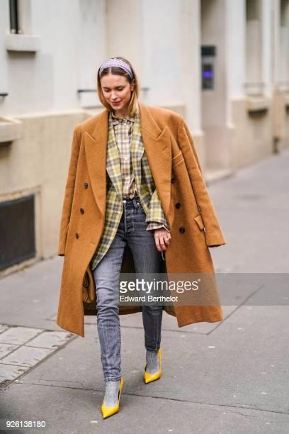 Pernille Teisbaek wears a brown coat a tartan jacket a checked shirt gray jeans yellow shoes during Paris Fashion Week Womenswear Fall/Winter...