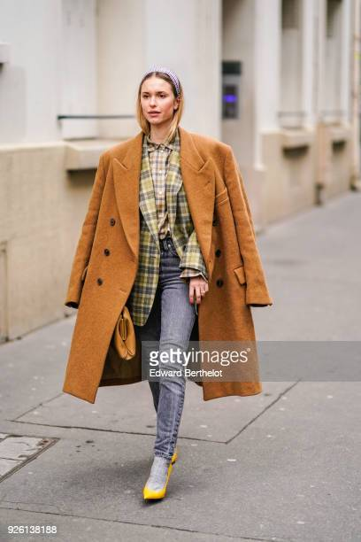 Pernille Teisbaek wears a brown coat a tartan jacket a checked shirt gray jeans yellow shoes during Paris Fashion Week Womenswear Fall/Winter...