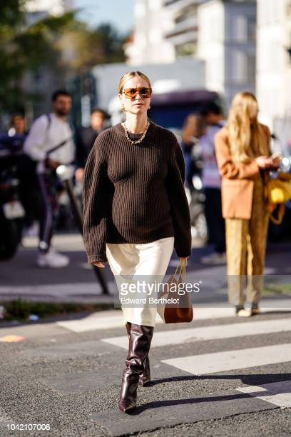 Pernille Teisbaek wears a brown wool pullover a white skirt brown leather boots outside Chloe during Paris Fashion Week Womenswear Spring/Summer 2019...