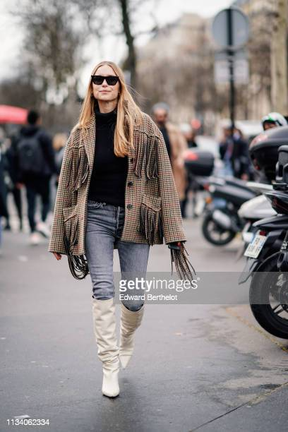 Pernille Teisbaek wears a checked jacket with fringes a black top gray denim pants white boots outside Miu Miu during Paris Fashion Week Womenswear...