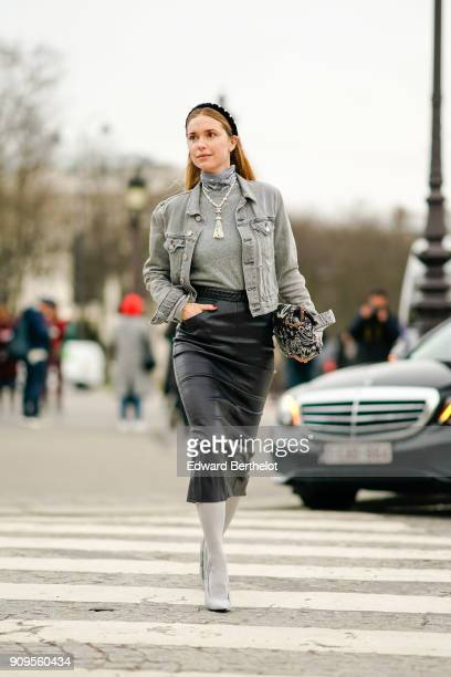Pernille Teisbaek wears a gray denim jacket a gray turtleneck a black leather dress a bag white boots outside Chanel during Paris Fashion Week Haute...
