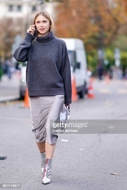 Pernille Teisbaek wears a gray turtleneck pull over, a gray skirt, silver shoes, outside Moncler, during Paris Fashion Week Womenswear Spring/Summer...