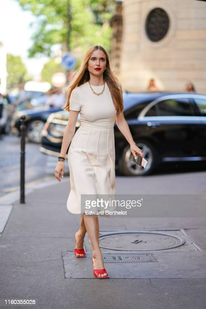 Pernille Teisbaek wears a necklace, a white dress, red shoes, bracelets, outside Valentino, during Paris Fashion Week -Haute Couture Fall/Winter...