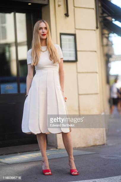 Pernille Teisbaek wears a necklace a white dress red shoes bracelets outside Valentino during Paris Fashion Week Haute Couture Fall/Winter 2019/2020...
