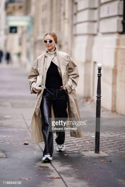 Pernille Teisbaek wears a trench coat, black leather pants, sneakers, outside Altuzarra, during Paris Fashion Week Womenswear Fall/Winter 2019/2020,...