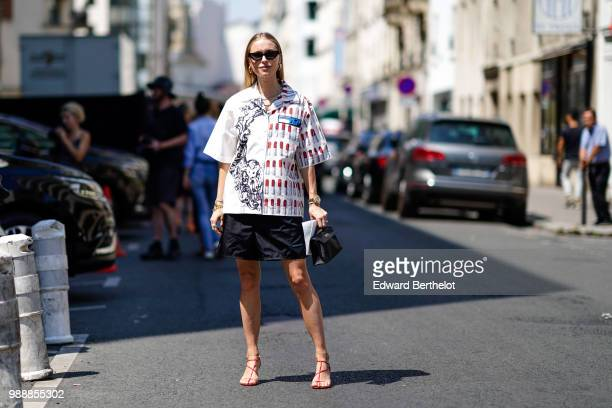 Pernille Teisbaek wears a white shirt with colored prints a black skirt sunglasses shoes a bag outside Acne Studios during Paris Fashion Week...